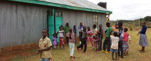 AIC Namuncha Child Development Center of Kenya children playing in front of water retention rain barrel