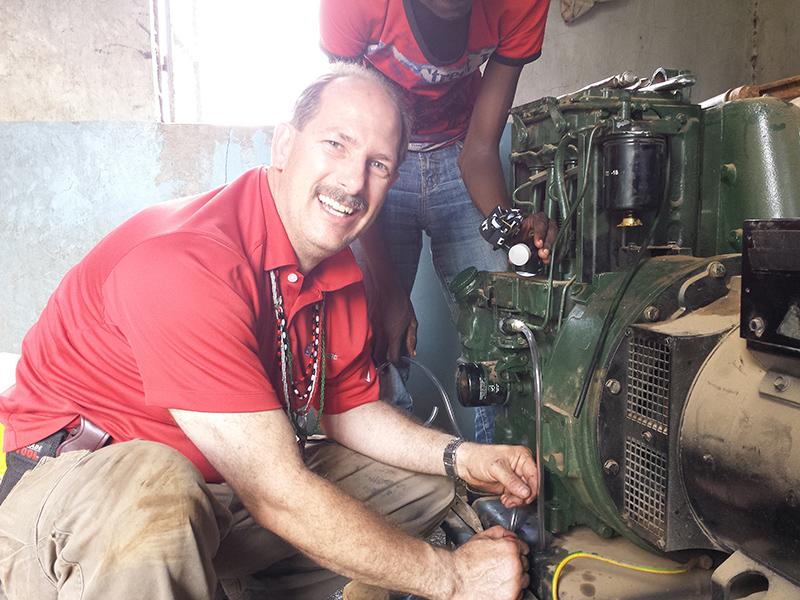 Clifford-Yantz-repairing-Ewauso-Kenya-well-pump-generator_800x600