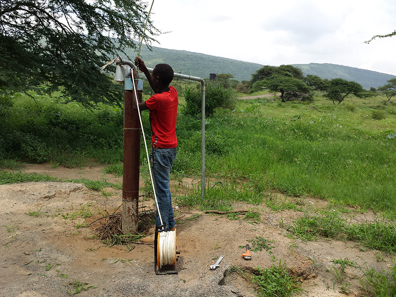 Maasai-youth-helping-repair-Ewauso-Kenya-well-connector-pump_800x600