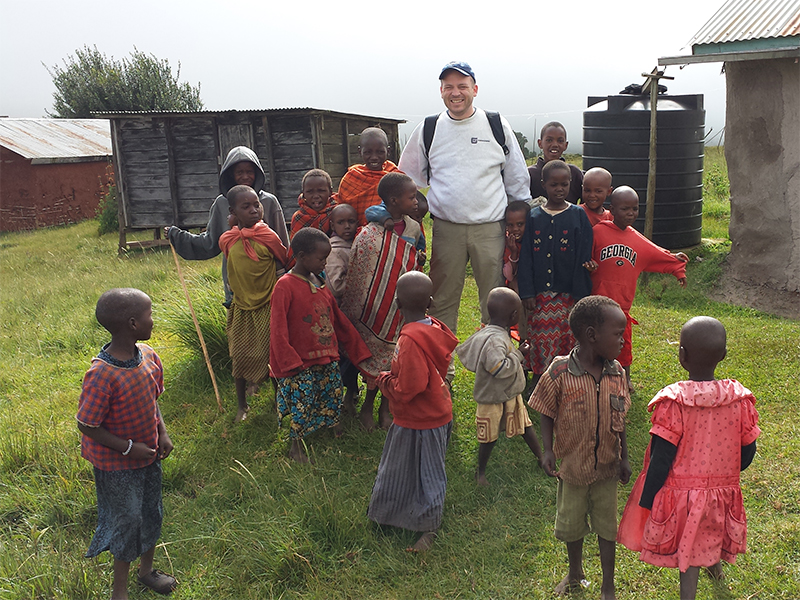 Matt-Maloney-with-Maasai-children-in-front-of-a-waterbarrel-we-installed