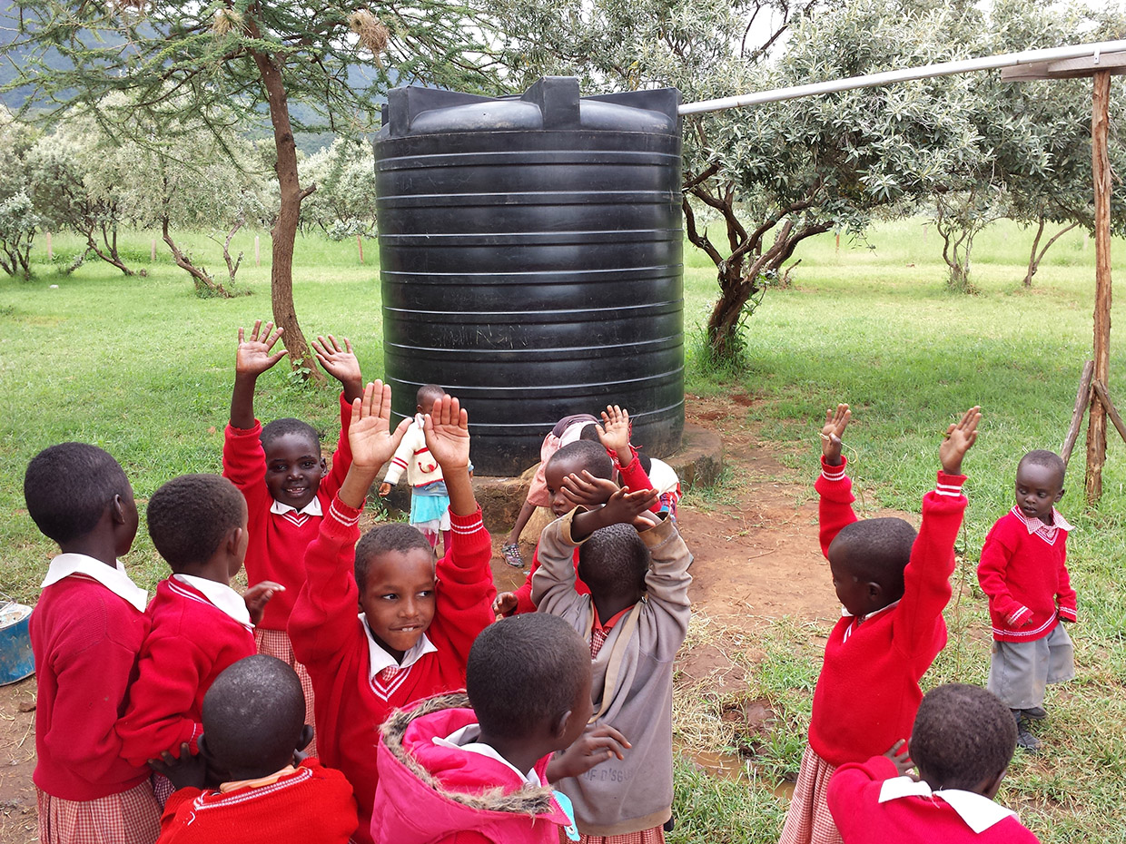 Namuncha-children-posing-with-hands-up-in-front-of-rainbarrel-smiling