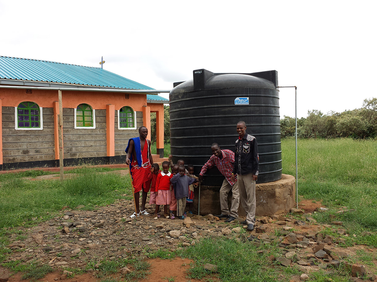 Solomon-with-school-teacher-and-children-in-front-of-rain-water-catching-rainbarrel